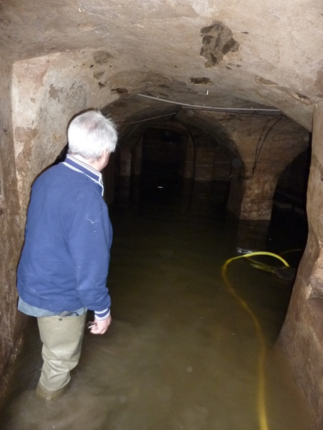 Mann mit Gummistiefeln in überschwemmtem Gewölbekeller