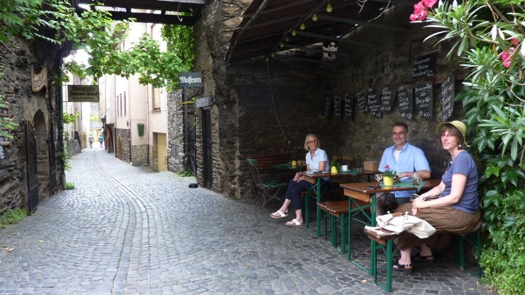 Gäste trinken Wein auf Bänken in der Altstadtgasse