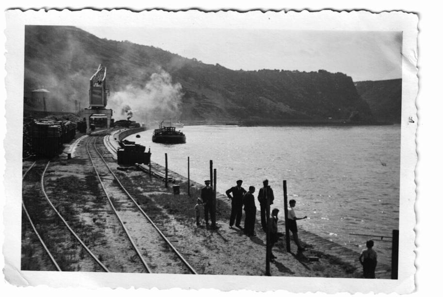 Häusener Kran am Rheinufer, Holzstöße zur Verladung, Frachtschiff, im Hintergrund der Loreleyfelsen