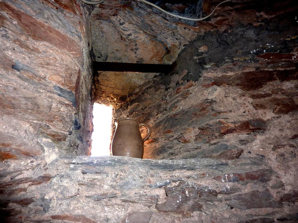 Tonkrug in einem kleinen Fenster in der mächtigen Bruchsteinwand des Stadtturms
