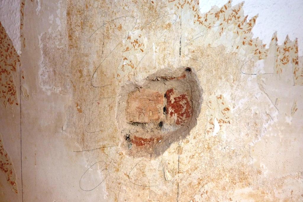 Backsteine sichtbar durch Öffnung im Putz