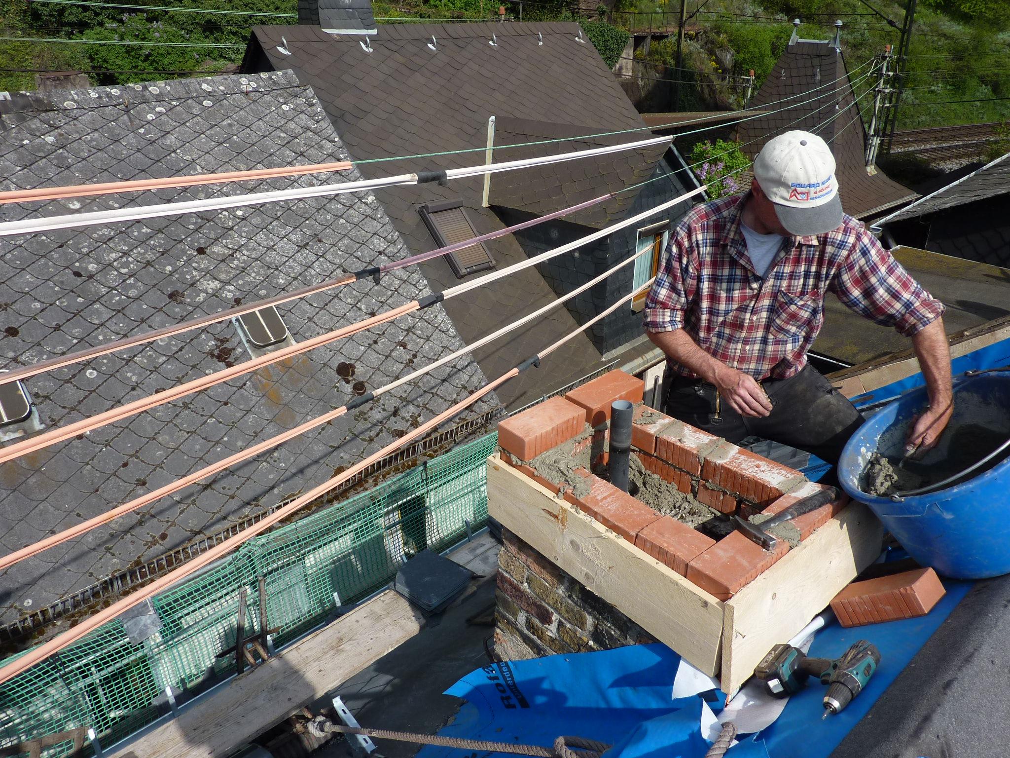Dachdecker auf dem Dach beim Mauern eines Kamins
