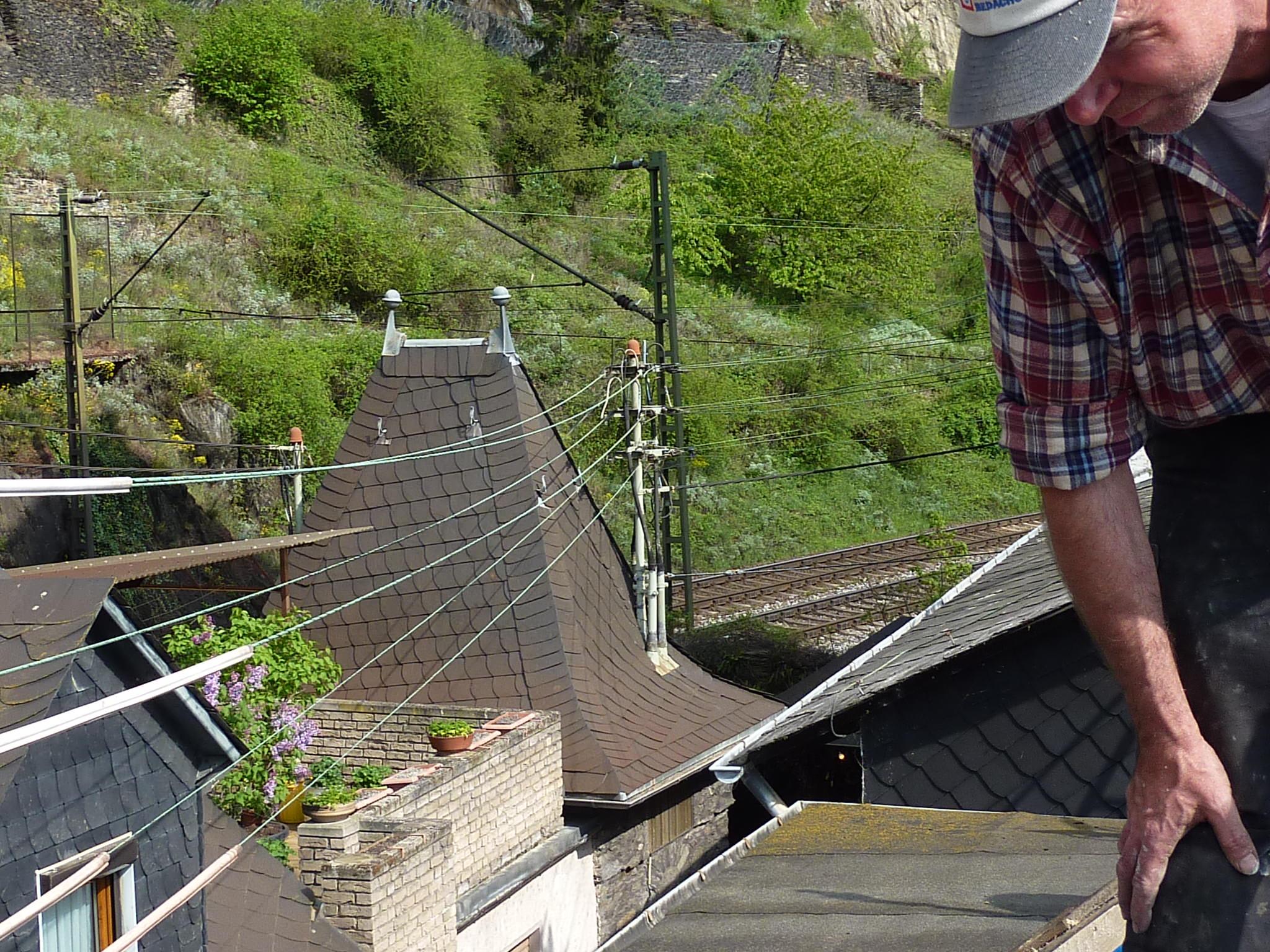 Kleine Dächer, enge Gasse, und gleich dahinter Bahntrasse und Berg