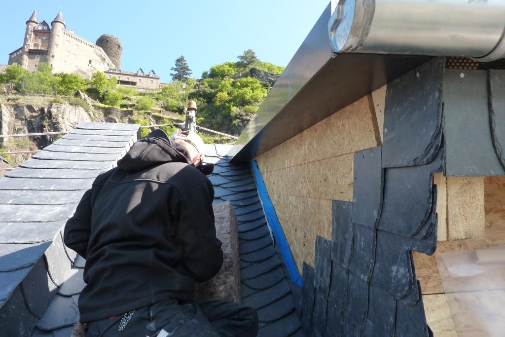 Dachdecker passt Schieferplatten an Gaubenwand an