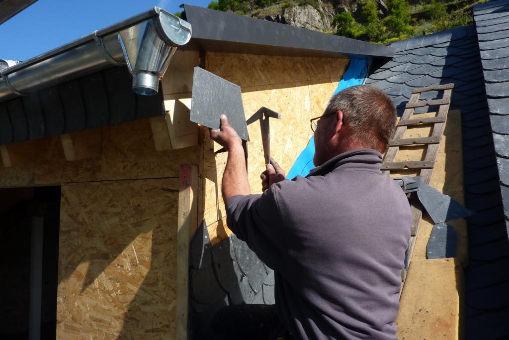 Dachdecker passt Schieferplatte an