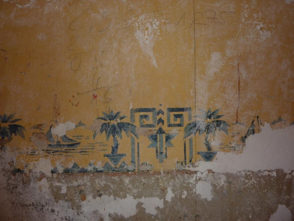 Blaue Ornamente mit Palmen und Segelboot auf geflickter Wand