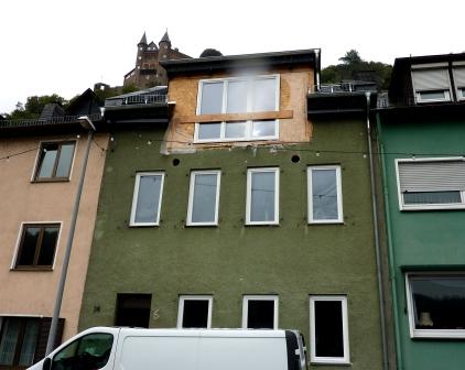 Fassade mit noch unverputzter Gaube und zwei runden Löchern.