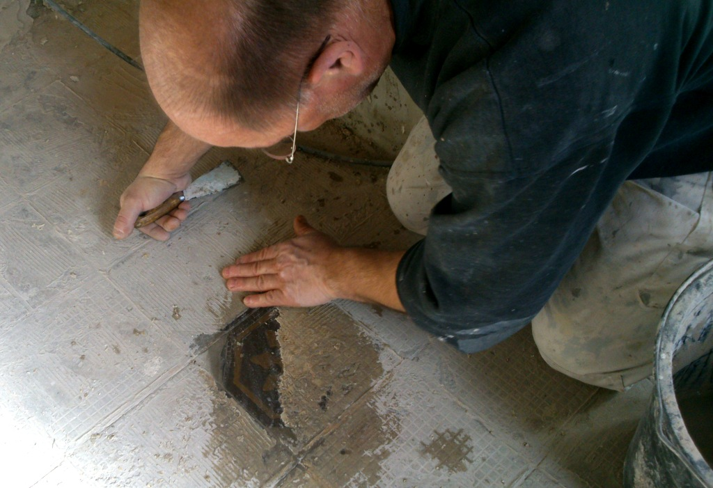 Mann kratzt Bodenfliese frei