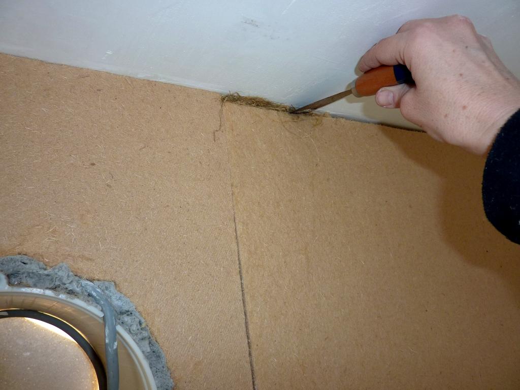 Hanffasern werden in Spalte zwischen Holzfaserdämmung und Zimmerdecke gestopft.