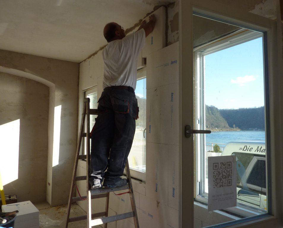 Handwerker auf der Leiter bringt weiße Platten an die Wand.