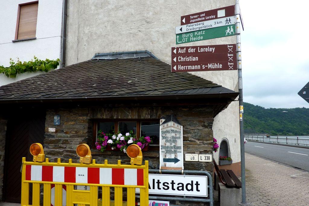 """Schild """"Baustelle"""" vor Stadtturm und touristischen Wegweisern"""