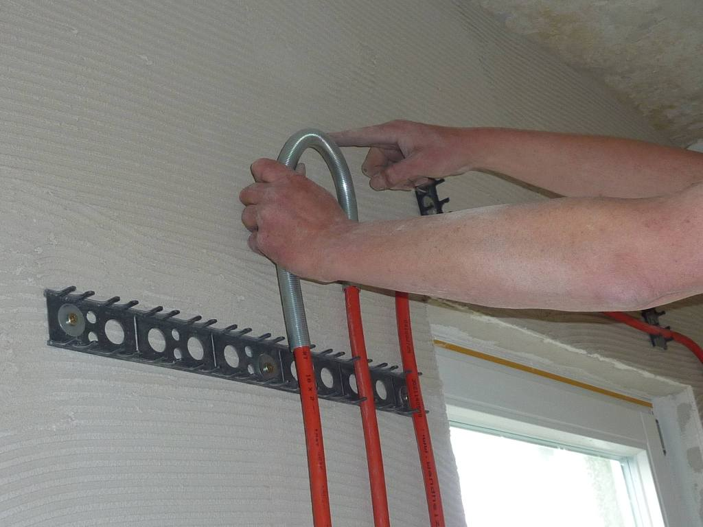 nah: Rohr wird auf Wand befestigt