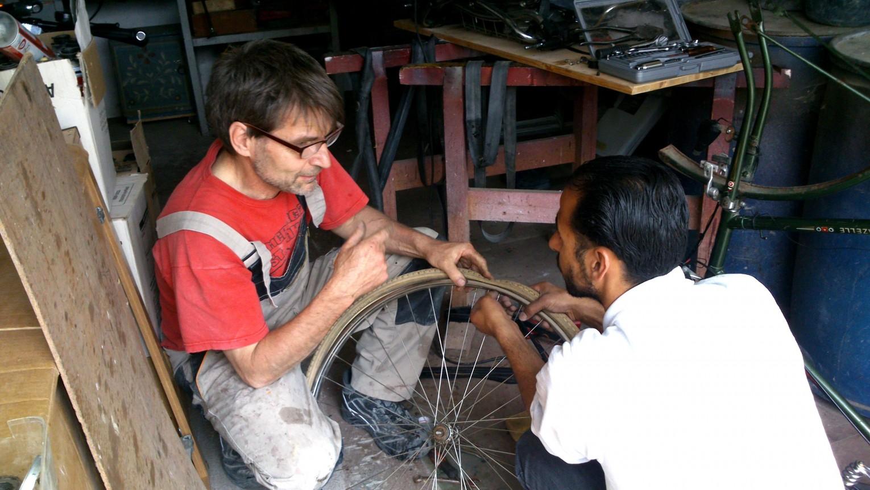Mann in Handwerkerkleidung und Mann aus Syrien beim Fahrradreifen reparieren.