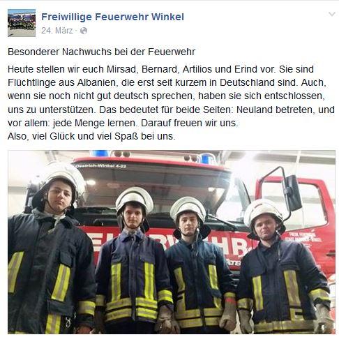 Vier junge Männer in Feuerwehr-Montur vor Einsatzwagen