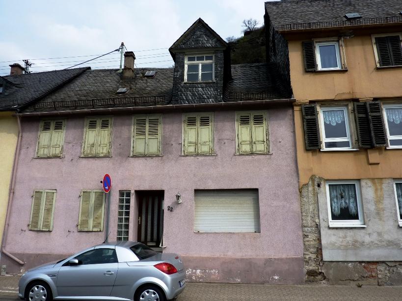 Altes kleines Haus Sankt Goarshausen, Rheinstraße 22 mit geschlossenen Fensterläden, von denen die Farbe abblättert. Fassade des Nachbarhauses ebenfalls in schlechtem Zustand