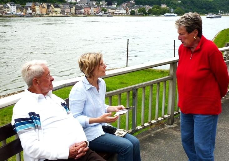 Eugen und Lore Kissel zeigen der Autorin Fotos am Rheinufer