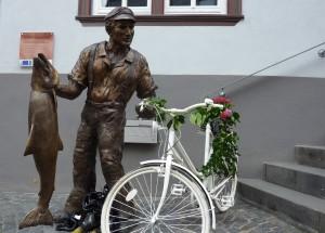 """Bronzeskulptur """"Ernst"""" mit geschmücktem Fahrrad"""