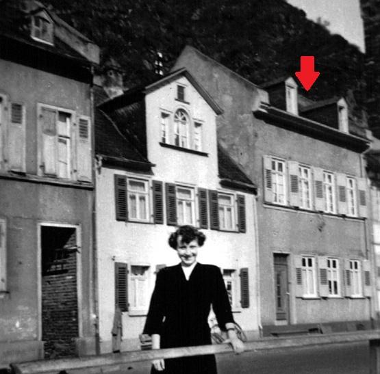 Lore Kissel vor Häuserzeile, ca. 1940, Pfeil auf Dach