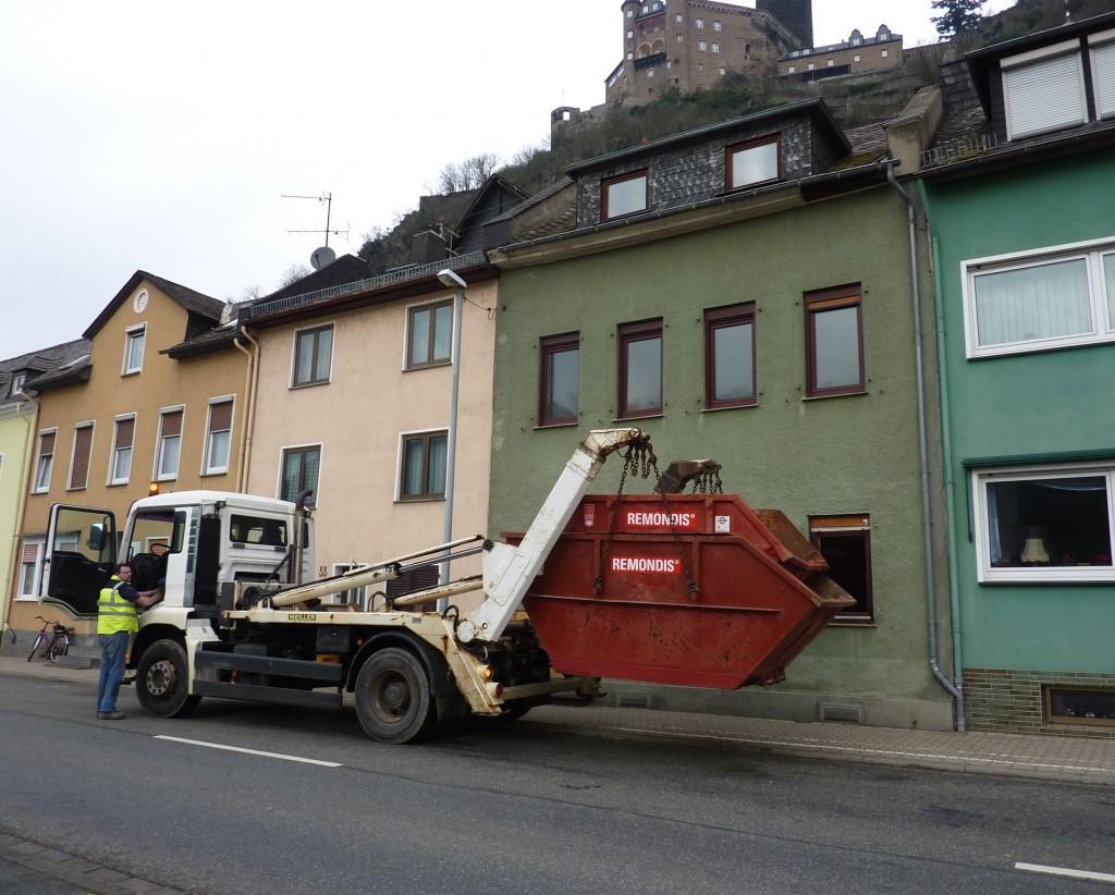 LKW-Fahrer lädt zwei Abfallcontainer ab.