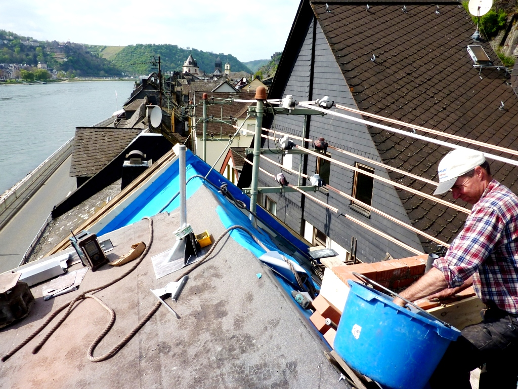 Ein Dachdecker bei der Arbeit über den Dächern der Altstadt von Sankt Goarshausen