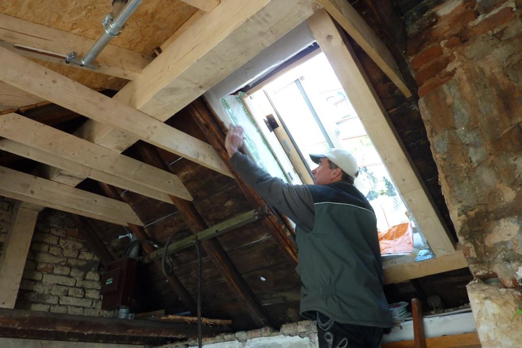 Dachdecker klebt Folie am Innenrand eines Dachfensters