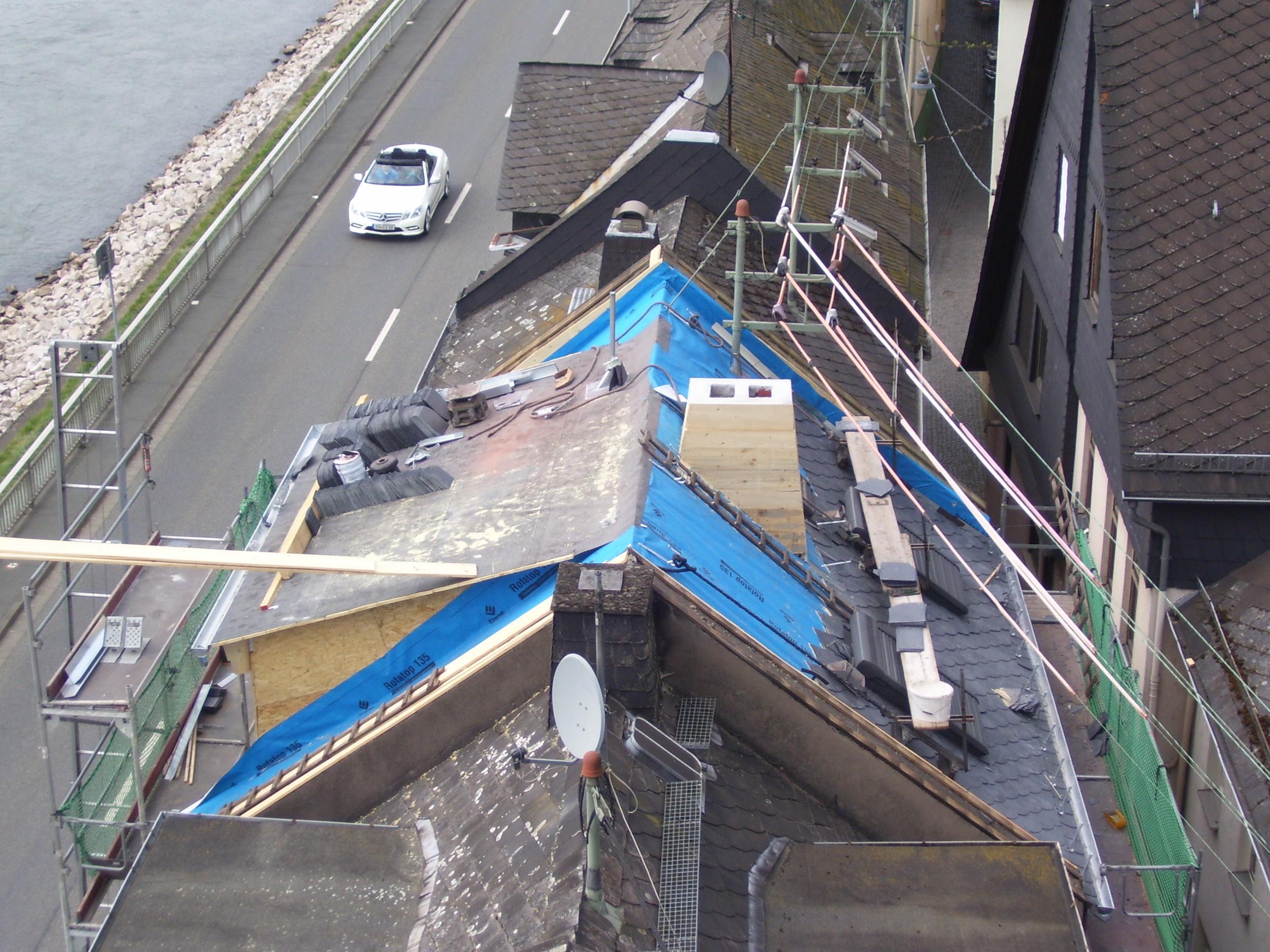Blick von schräg oben auf halb gedecktes Dach mit Baumaterial