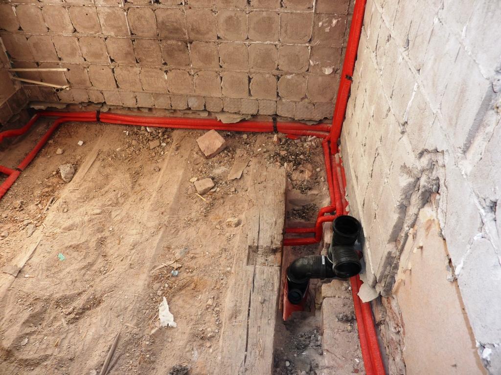 Fußboden Balken mit Sandschüttung, neue Rohre mit roter Isolierung