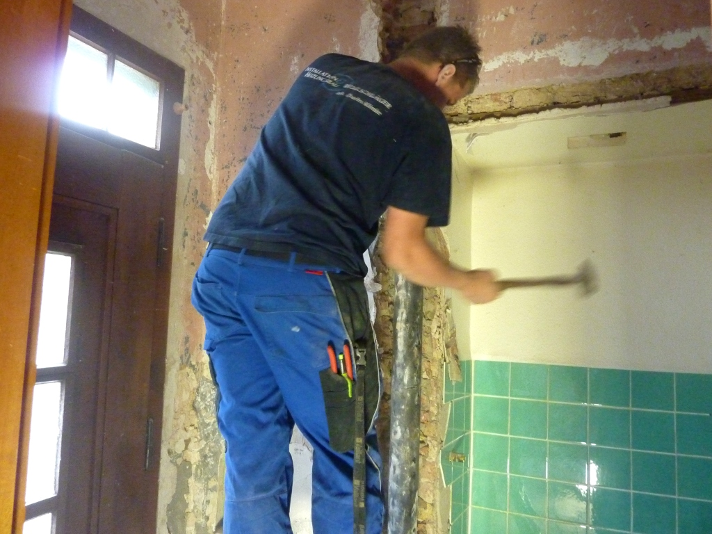 Handwerker schwingt Hammer gegen Rohr in aufgebrochener Wand