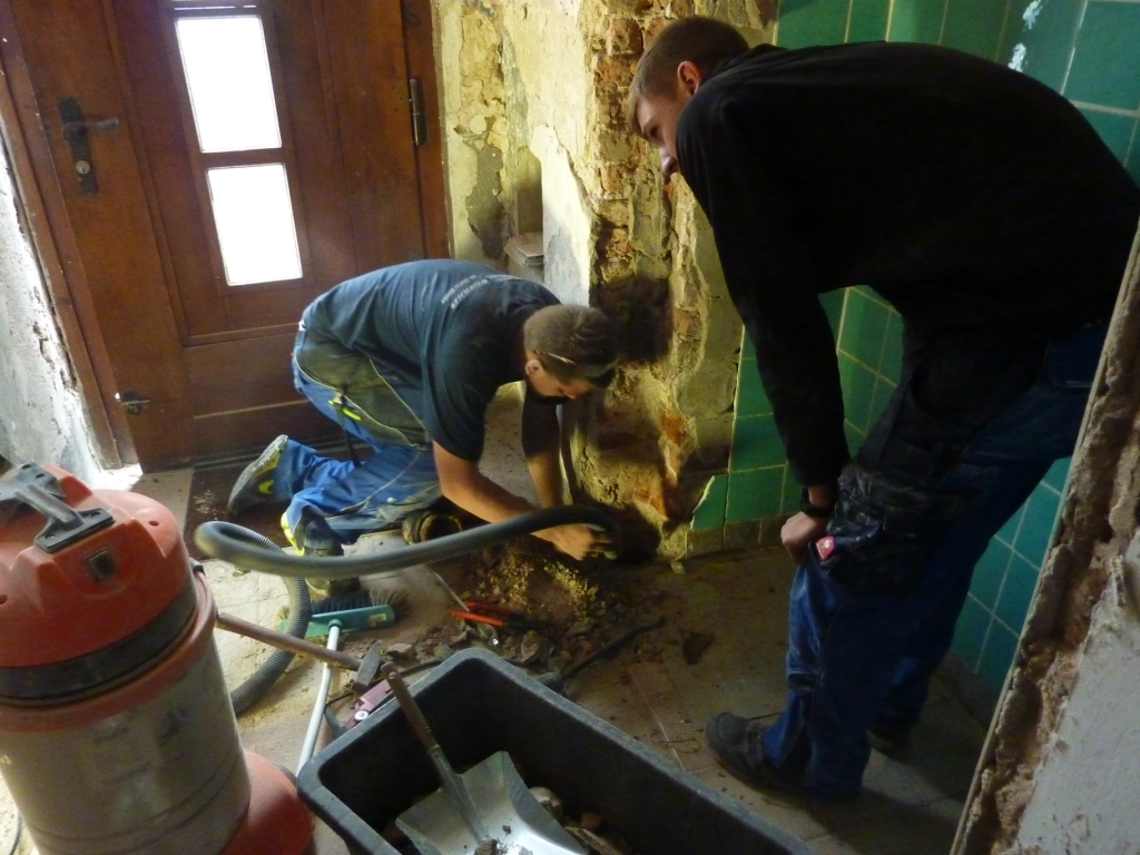 Handwerker saugt Schutt ab mit großem Staubsauger