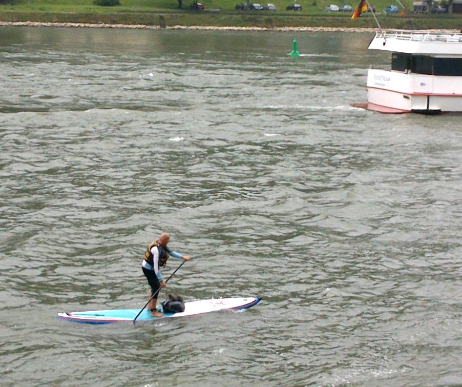 Mann mit Paddel auf Surfbrett, auf dem Rhein