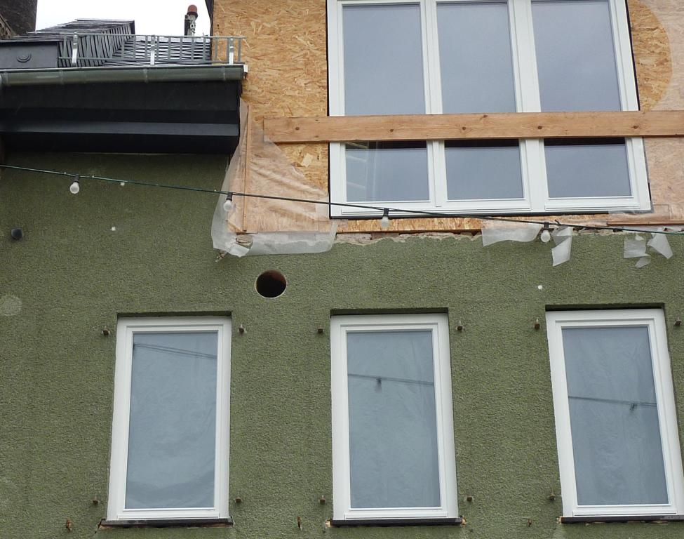 rundes Loch in Fassade oberhalb einer Fensterreihe