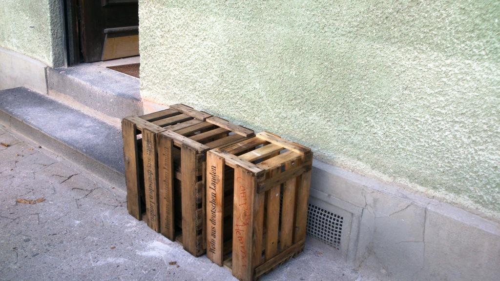 Vier hölzerne Kisten auf Gehweg neben Haus-Eingang