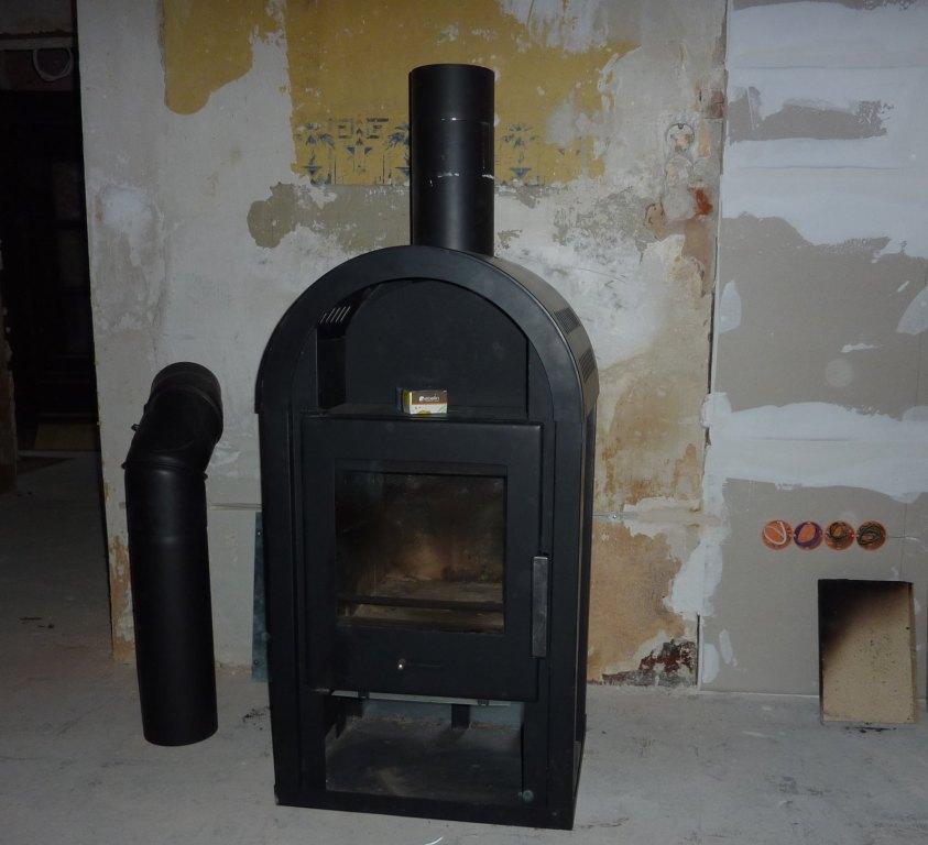 Schwarzer Kaminofen vor unverputzer Wand, daneben ein Teil des Ofenrohrs