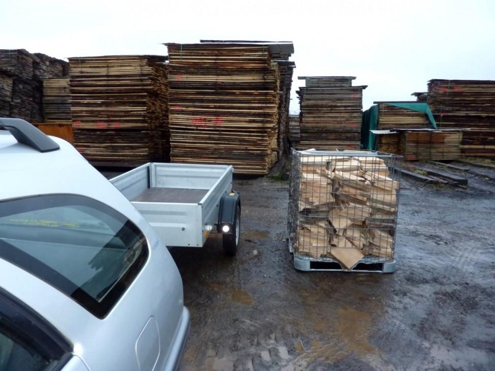 Holz in Gitterbox neben Auto mit Hänger