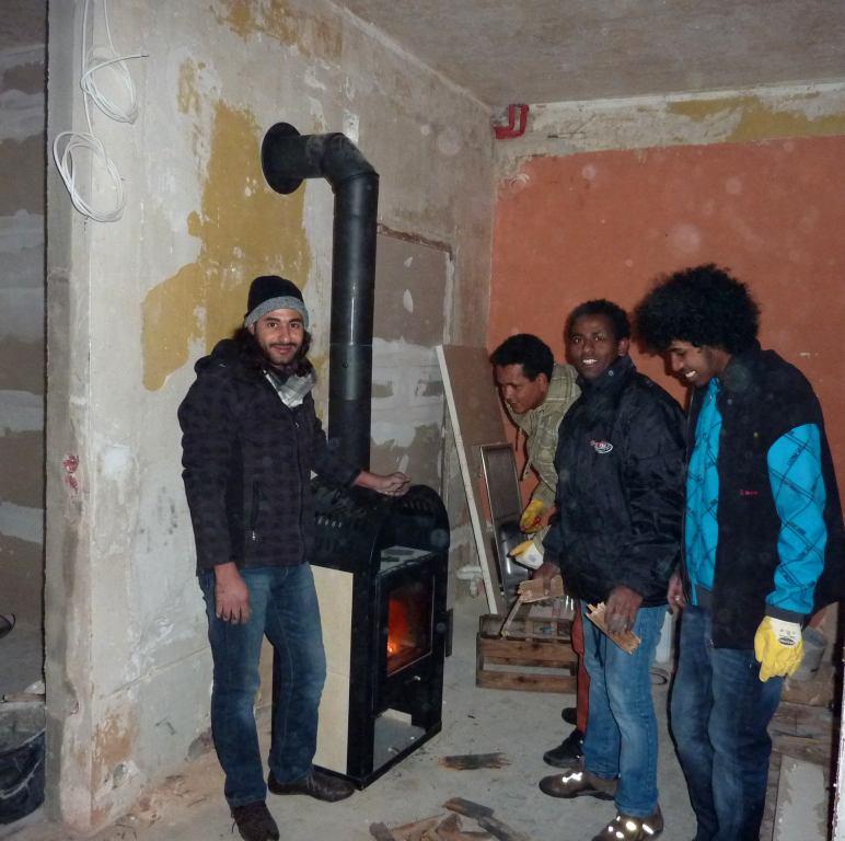 Vier Afrikaner und ein Feuer im Ofen auf Baustelle