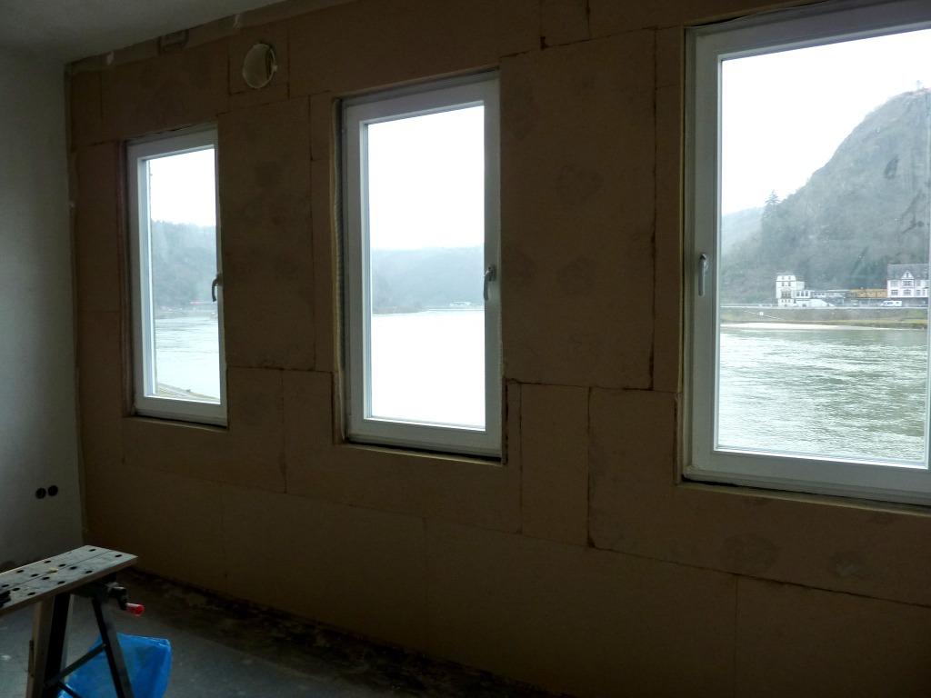 Wand, rund um und zwischen den Fenstern mit Holzfaserplatten verkleidet