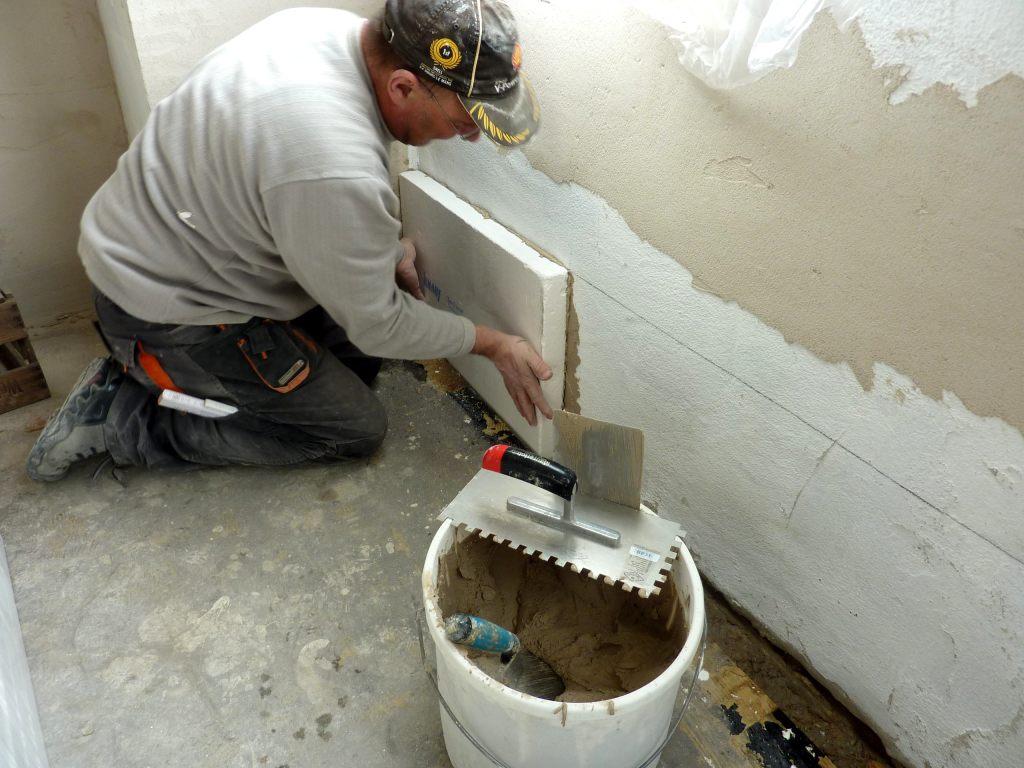 Handwerker klebt weiße Mineralschaumplatte an die Wand.