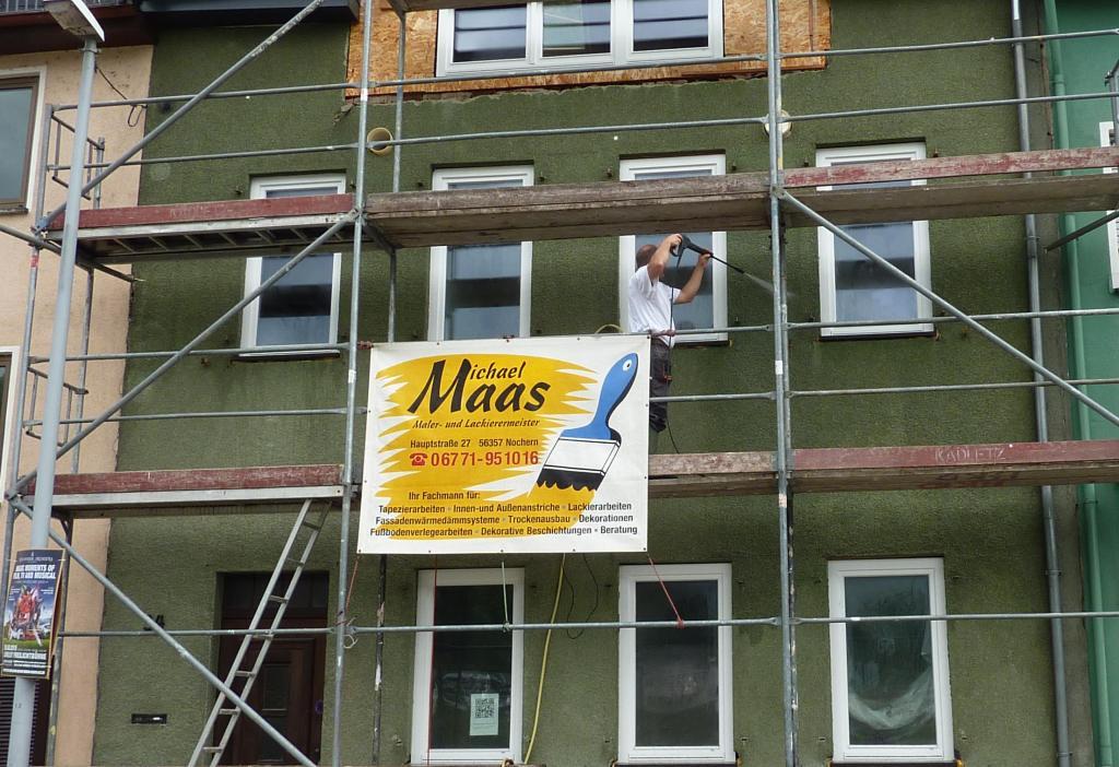 Handewerker mit Hochdruckreiniger an Hausfassade