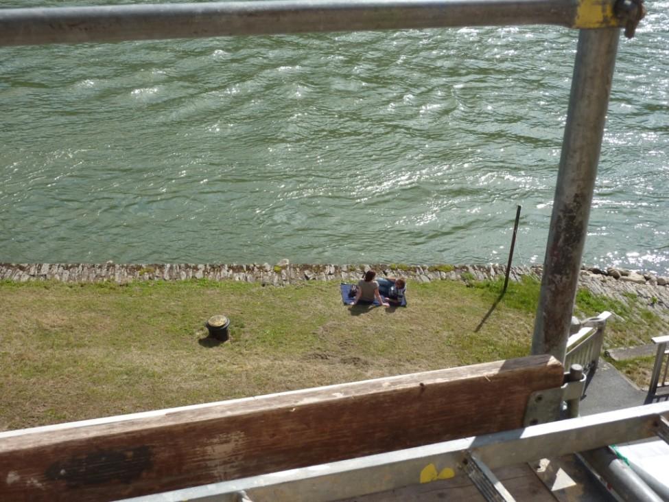 Zwei Personen sitzen auf Wolldecke am Rheinufer