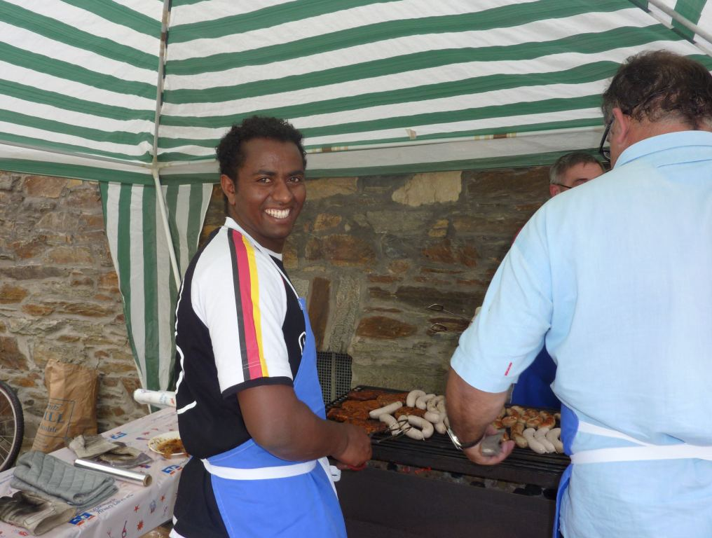 Eritreer hilft beim Würstchen Grillen.