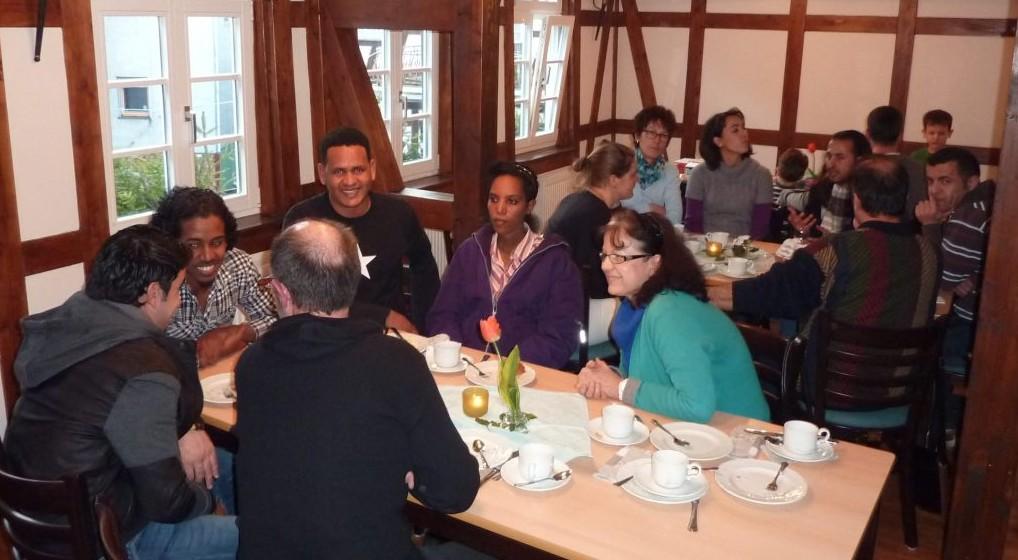 Junge Afrikaner mit Einheimischen an einer Kaffeetafel.