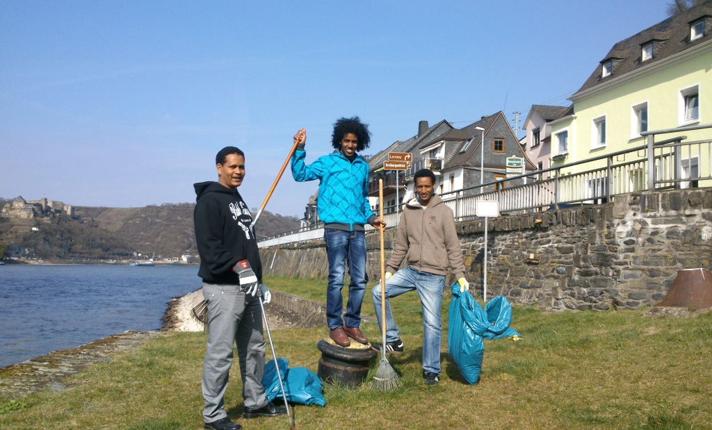 Drei junge Eritreer mit Müllsächen und Besen am Rheinufer