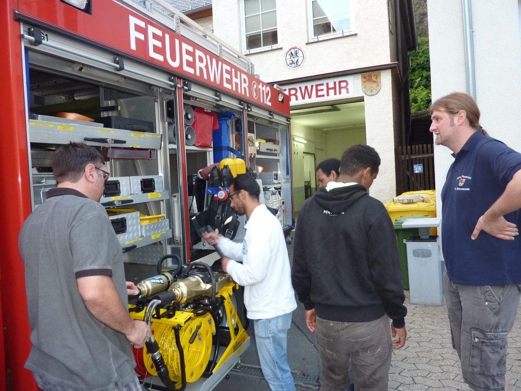 Feuerwehrleute und Flüchtlinge an einem offenen Feuerwehr-Fahrzeug