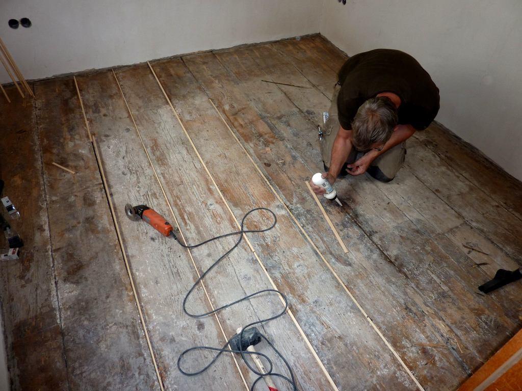 Handwerker fügt neue Weichholzleisten in alten Dielenboden ein.